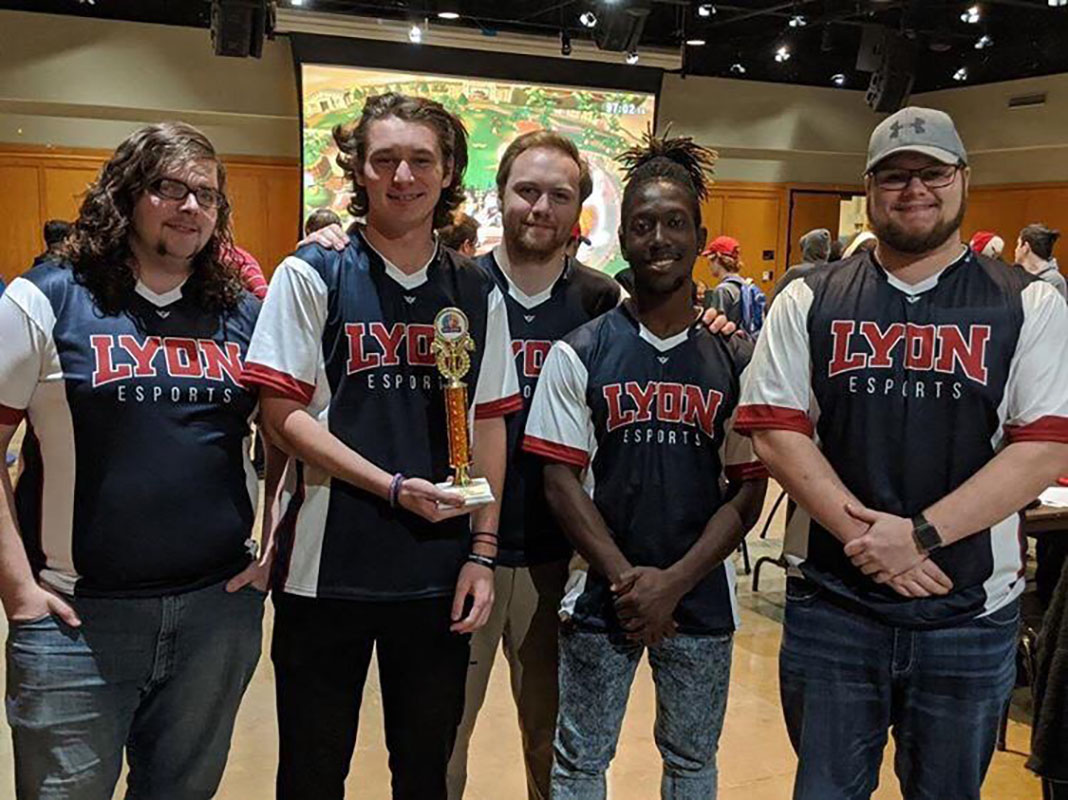 Four students and their coach pose for a photograph in their Lyon College eSports jerseys