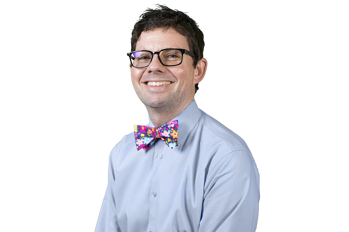 Photograph of man wearing eyeglasses and a colorful bow tie.