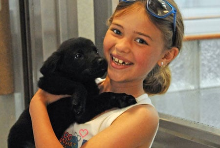 Small girl with brown hair holding a black dog