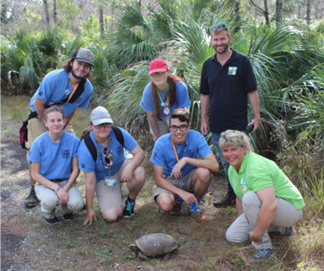 Dr. Whitfield and Nicole Atteberry with Conservation Teen Scientists gathered around a gopher tortoise