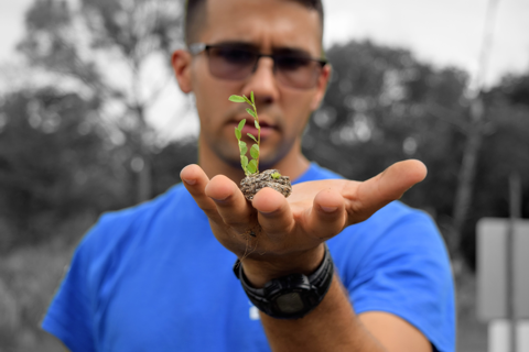 FIU intern Adrian holding gopher tortoise scat that has a pine rockland plant growing out of it.
