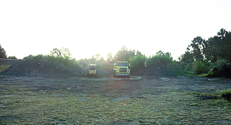trucks clearing fill and invasive plants at first restoration site