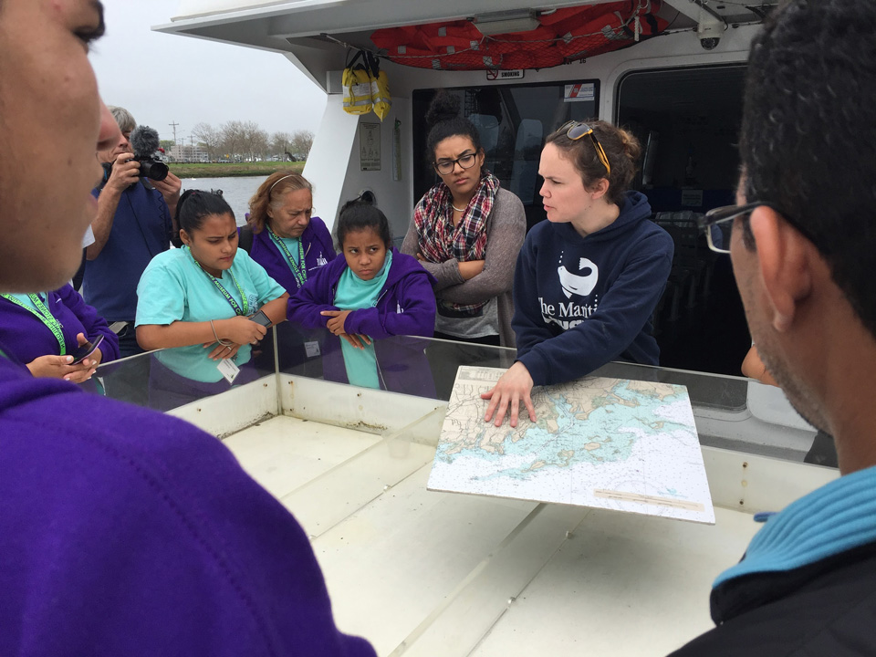 Maritime Aquarium leader teaching a lesson to students on a boat.