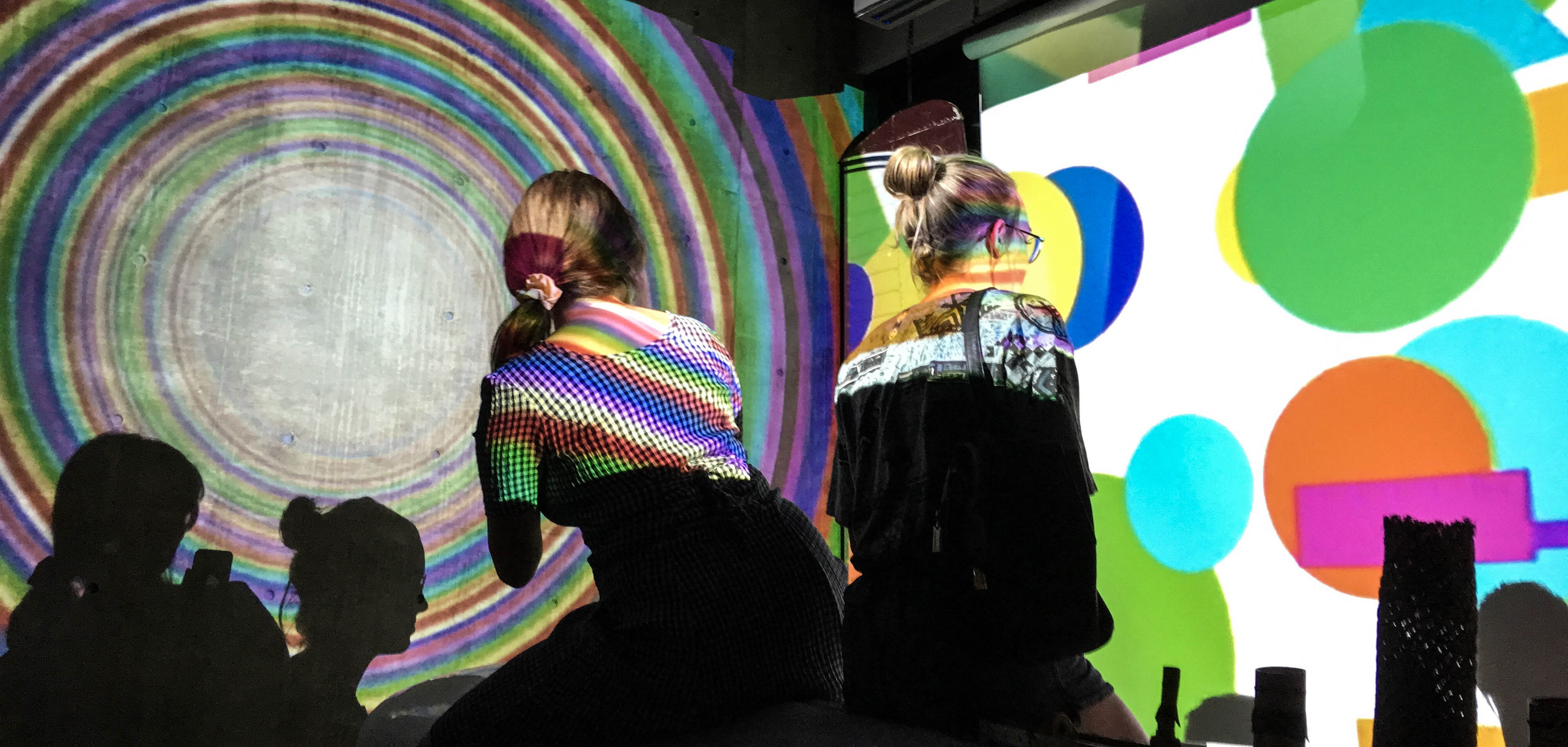 Two girls look at colorful lights at an exhibit in Tulsa's downtown art museum, ahha.