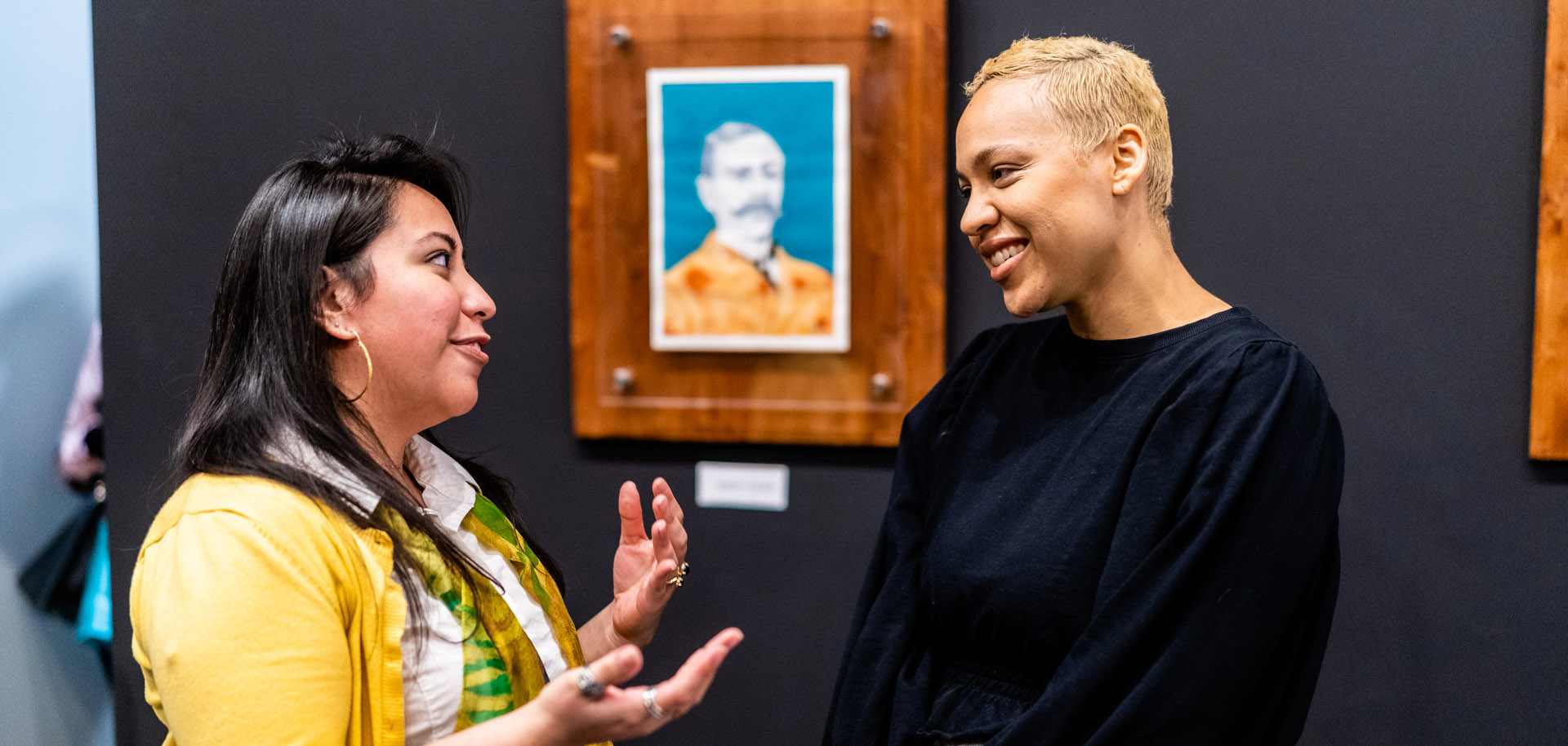 Two people talk at the re-opening of Black Wall Street Gallery in Tulsa's Greenwood District in March 2020.