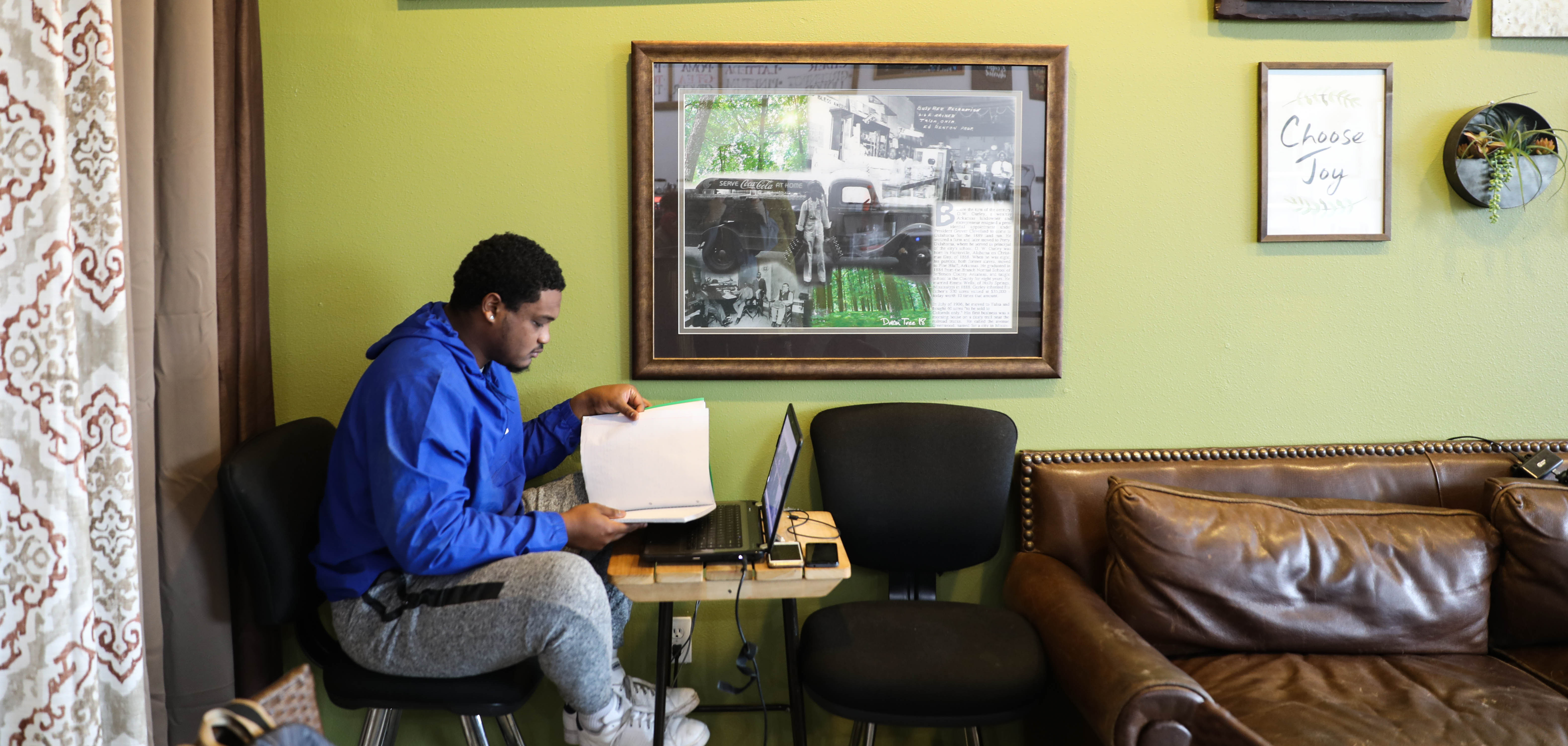 A man looks through paperwork with his laptop out and phone charging inside Black Wall Street Liquid Lounge, a vibrant coffee shop located in the Greenwood District in downtown Tulsa, Oklahoma.