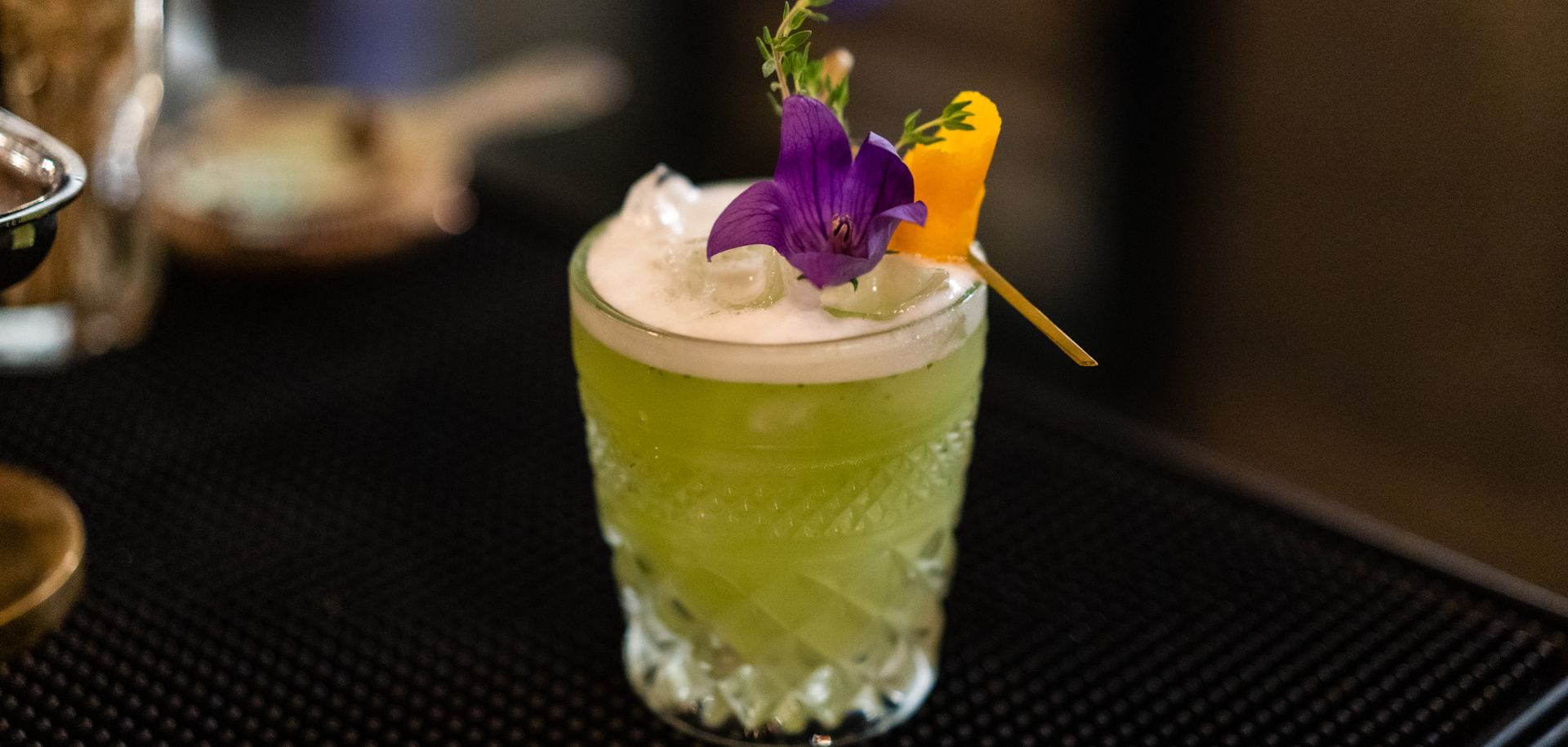A green cocktail with an edible purple flower at Boston Title and Abstract in downtown Tulsa's Deco District.