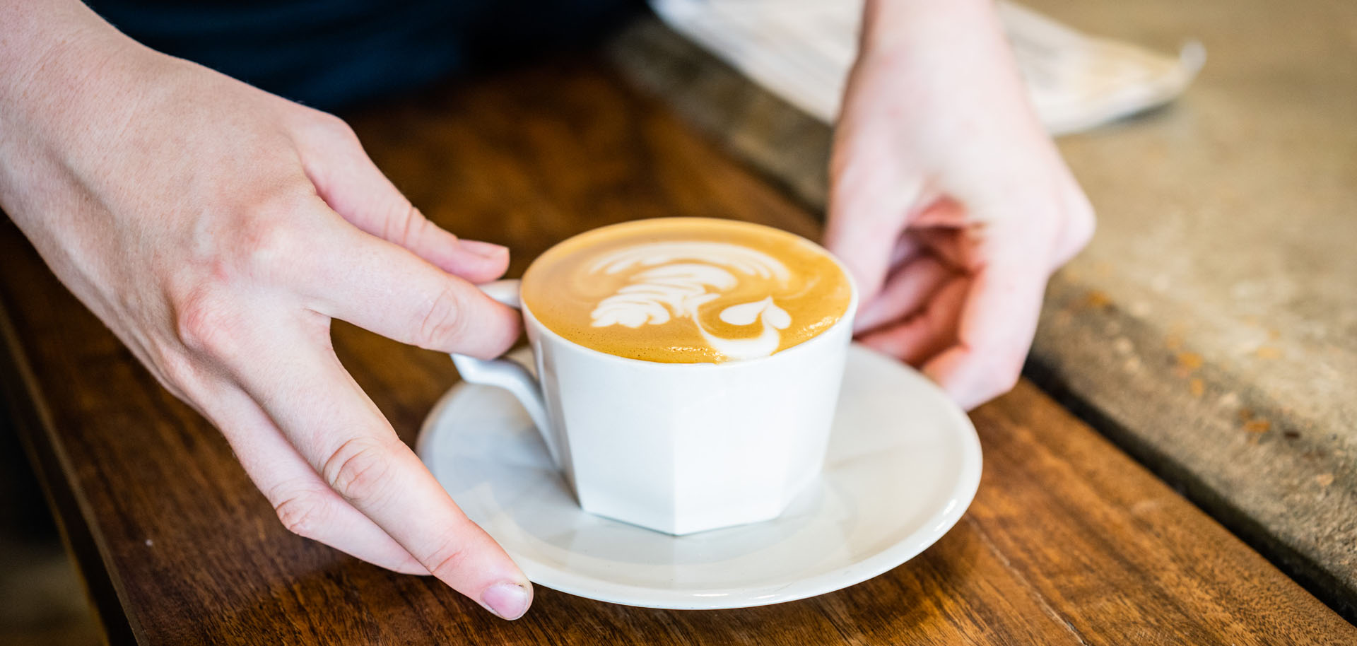 A person holds a latte in a white mug at Cirque Coffee in Tulsa's Pearl District