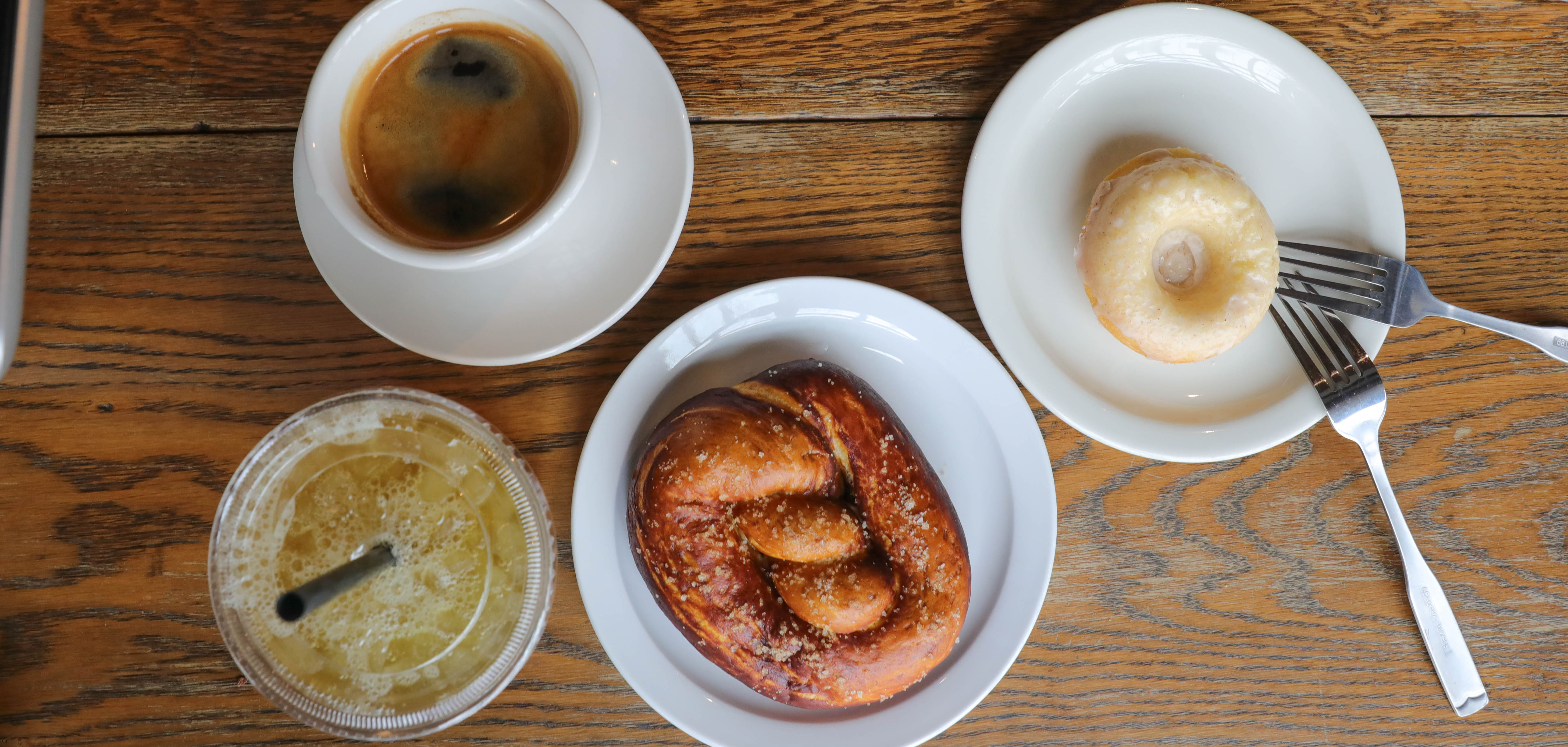 A pretzel, donut, coffee, and iced tea sit on a wooden table at DoubleShot Coffee in Tulsa, Oklahoma.