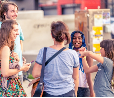 A group of teenagers talk at the First Friday Art Crawl event in the Tulsa Arts District in downtown Tulsa, Oklahoma.