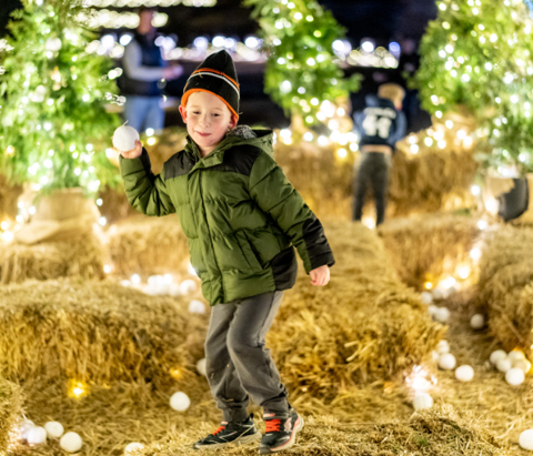 A boy throws a snowball during the Garden of Lights event at Tulsa Botanic Garden.