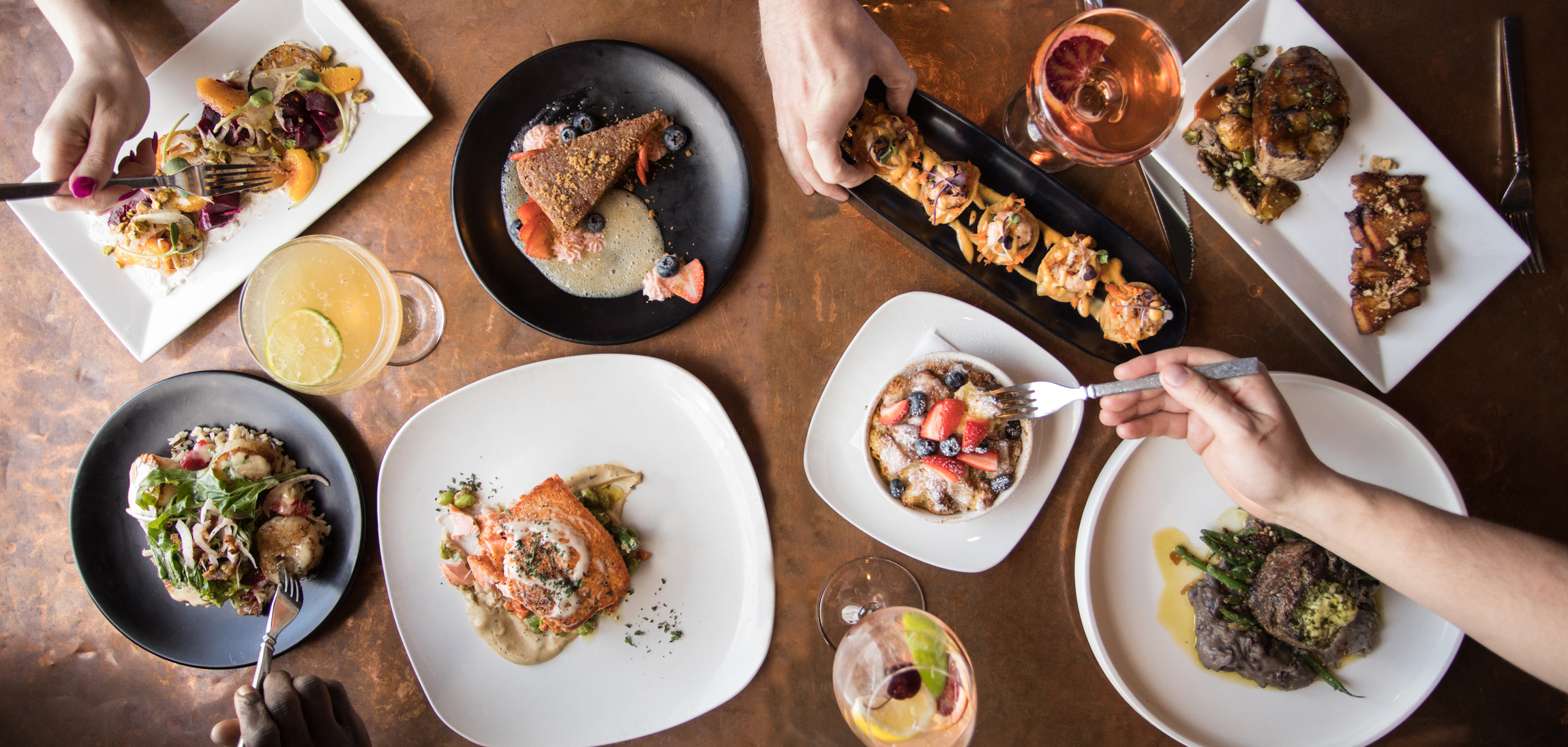 An overhead shot of food and drinks at the upscale American fare restaurant, Juniper, in Tulsa's Blue Dome District.