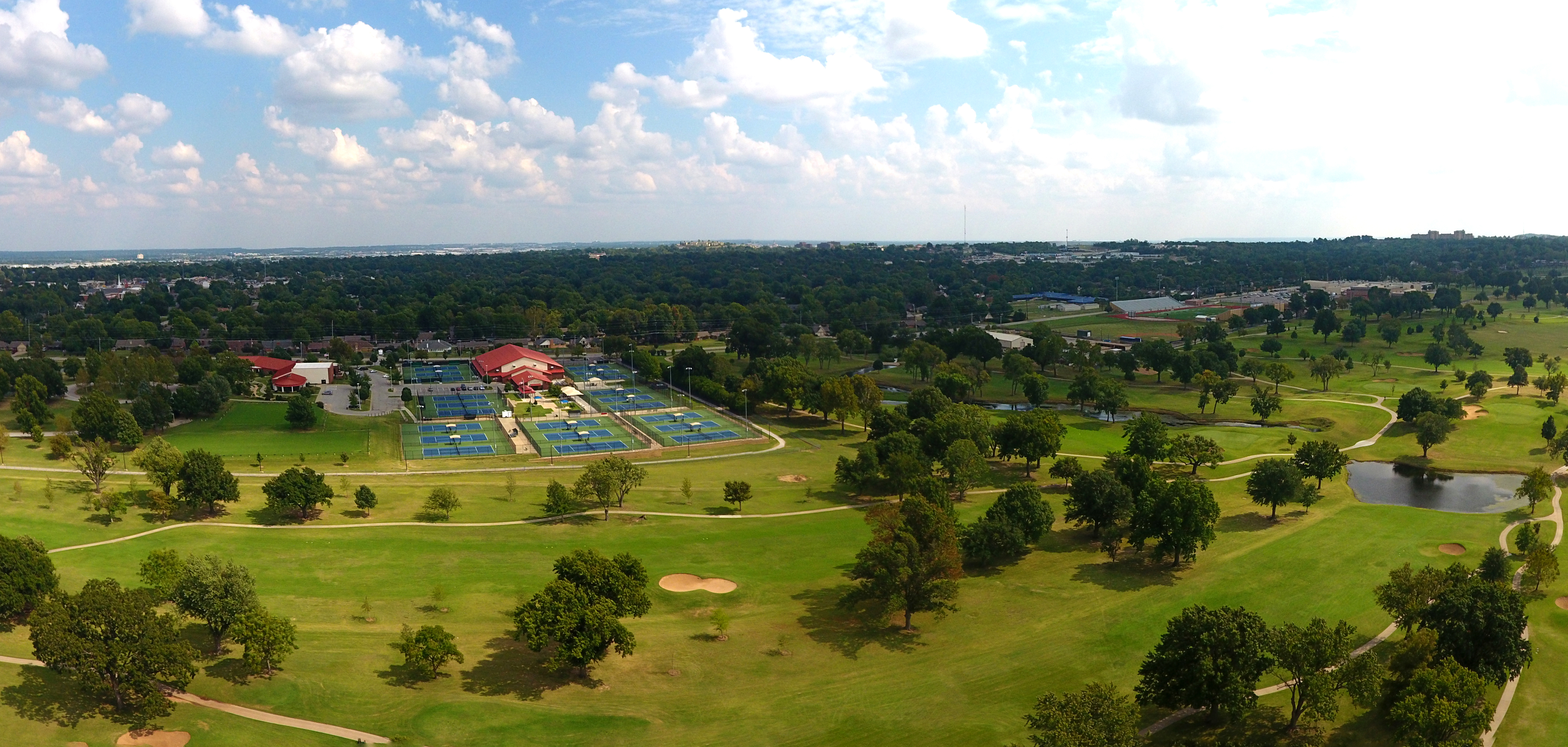 An aerial view of LaFortune Park with the golf course, tennis courts, and trees in view.