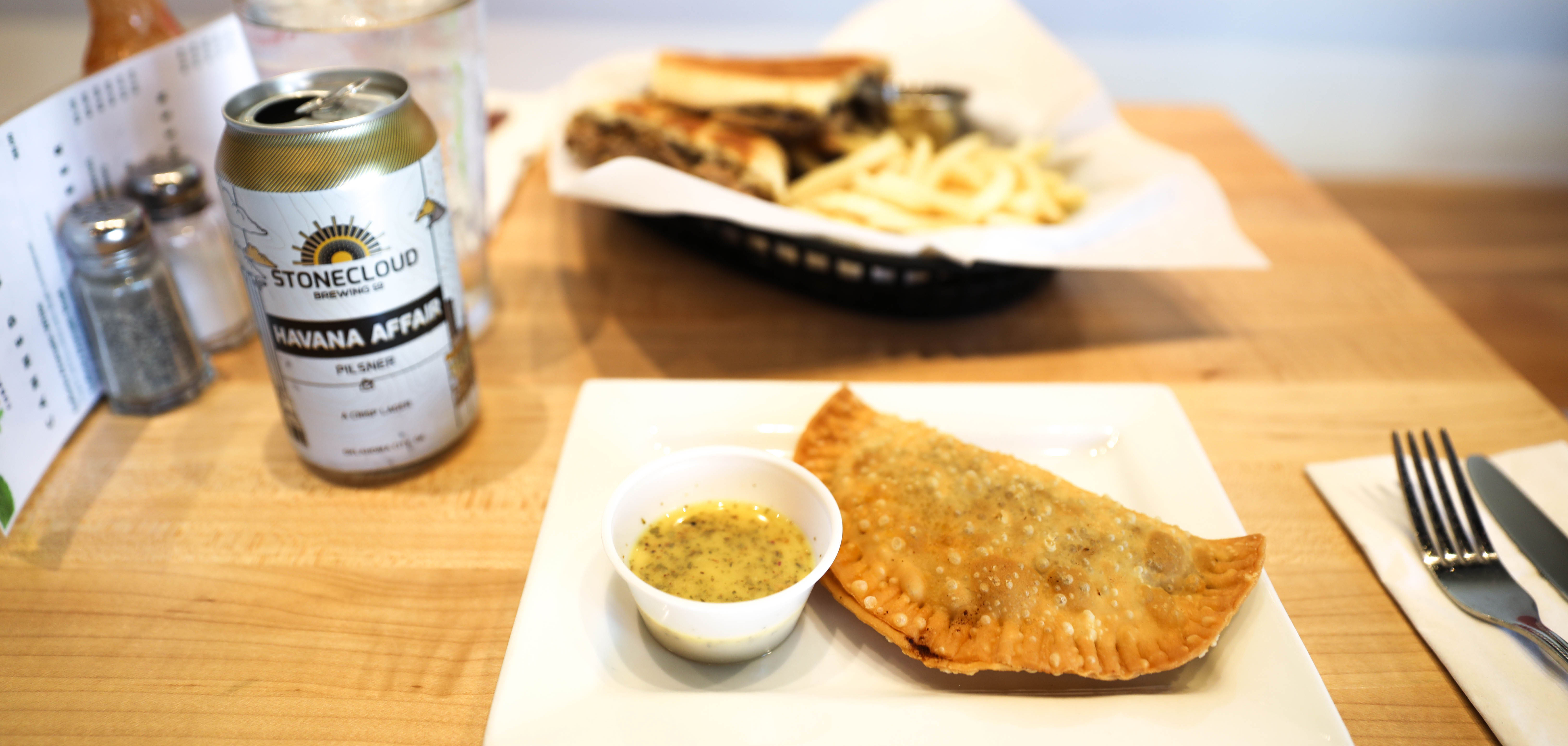 Empanadas sit on a table next to a Stonecloud beer at Mangos Cuban Cafe in Tulsa, Oklahoma.