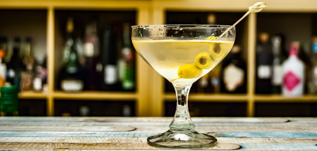 A martini sits on a table at a bar during happy hour.