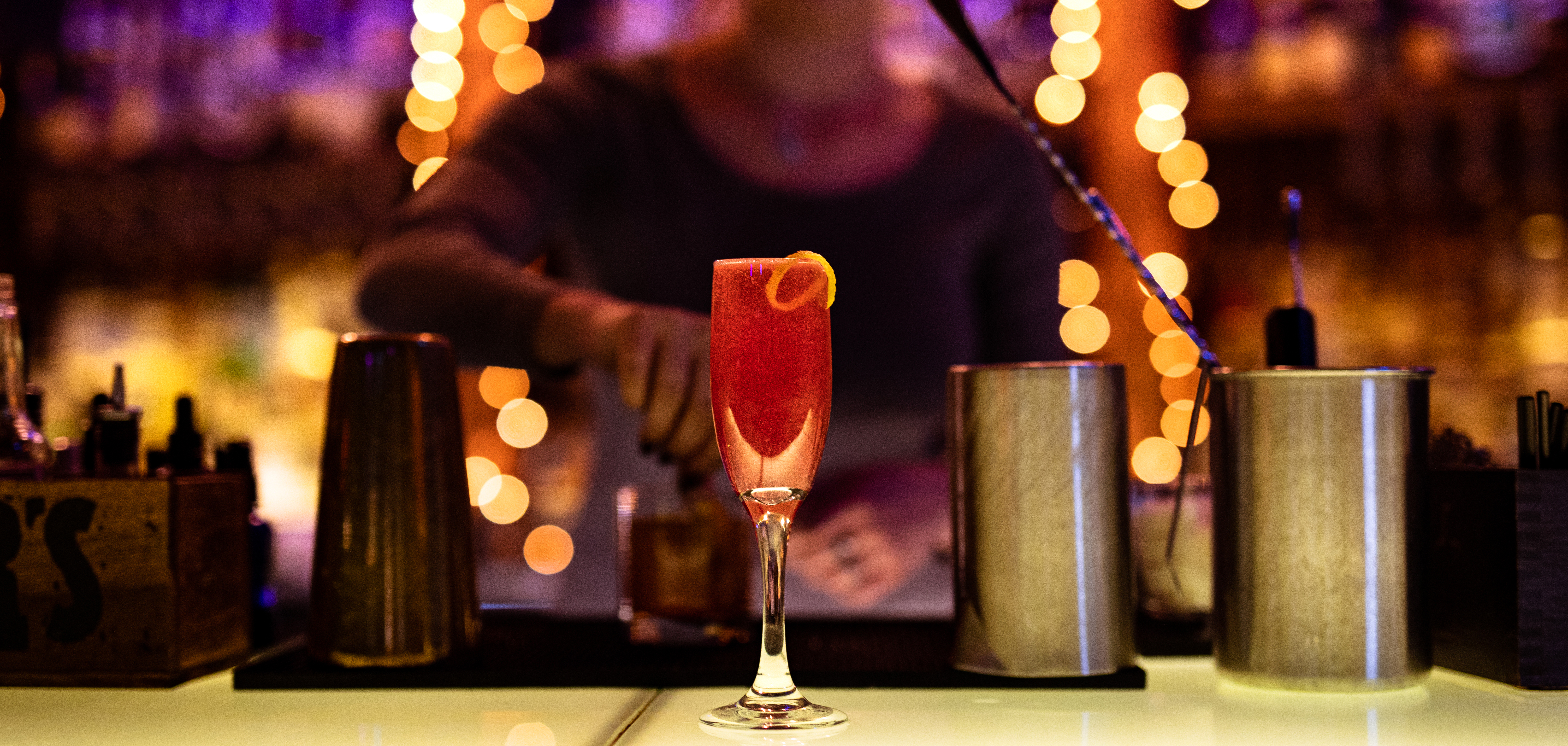 A red cocktail in a champagne glass sits atop the MixCo bar.