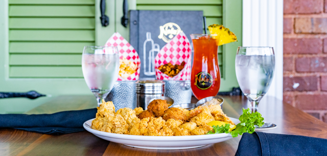 $8 hurricanes, $12 fried platter, $3 popcorn, and $4 roasted nuts at Nola's Creole on Cherry Street in Tulsa, Oklahoma.