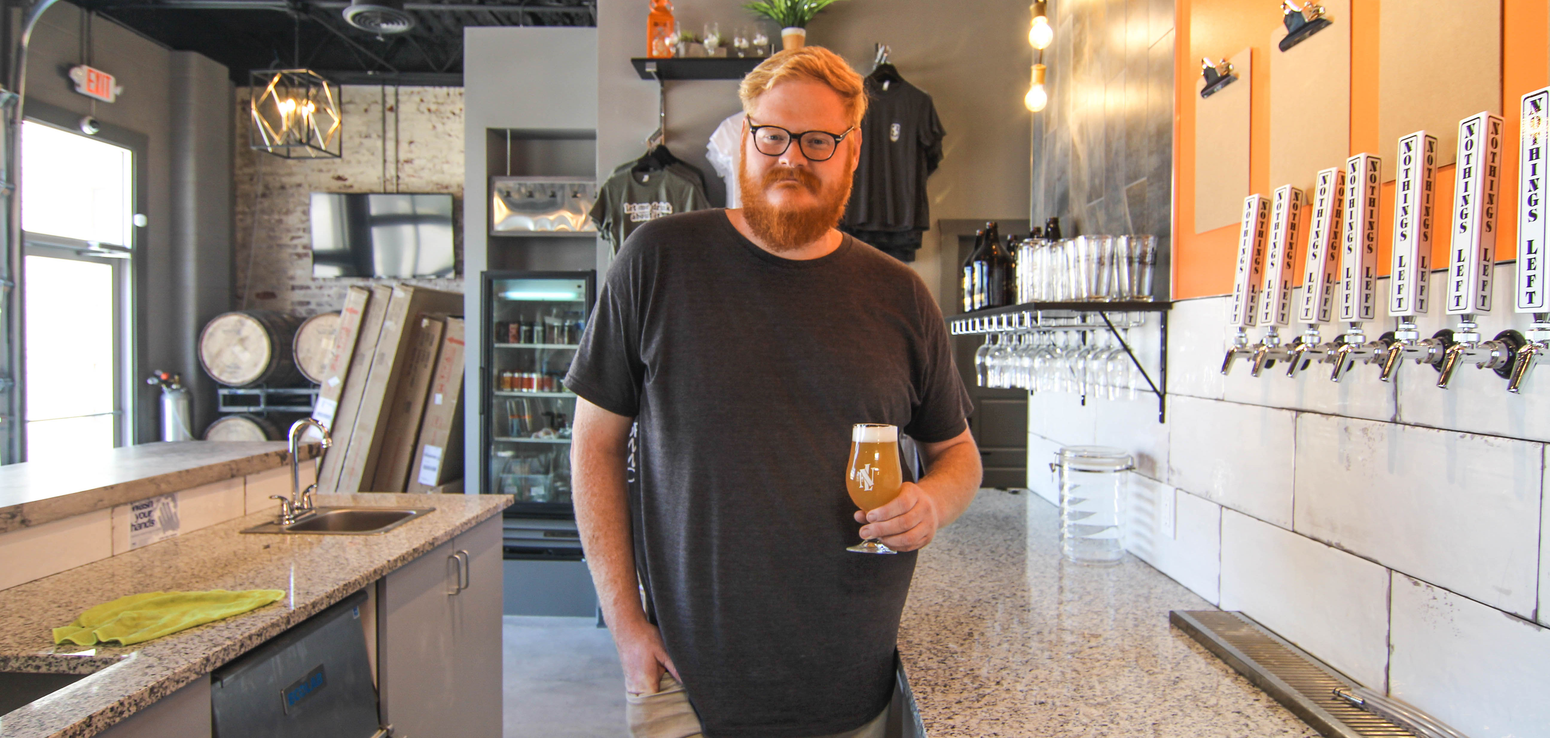 Owner Travis Richards holds a beer at his brewery, Nothing's Left Brewing Company.