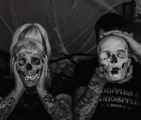 Oddities and curiosities founders holding skulls in front of their faces. Tulsa, Oklahoma.