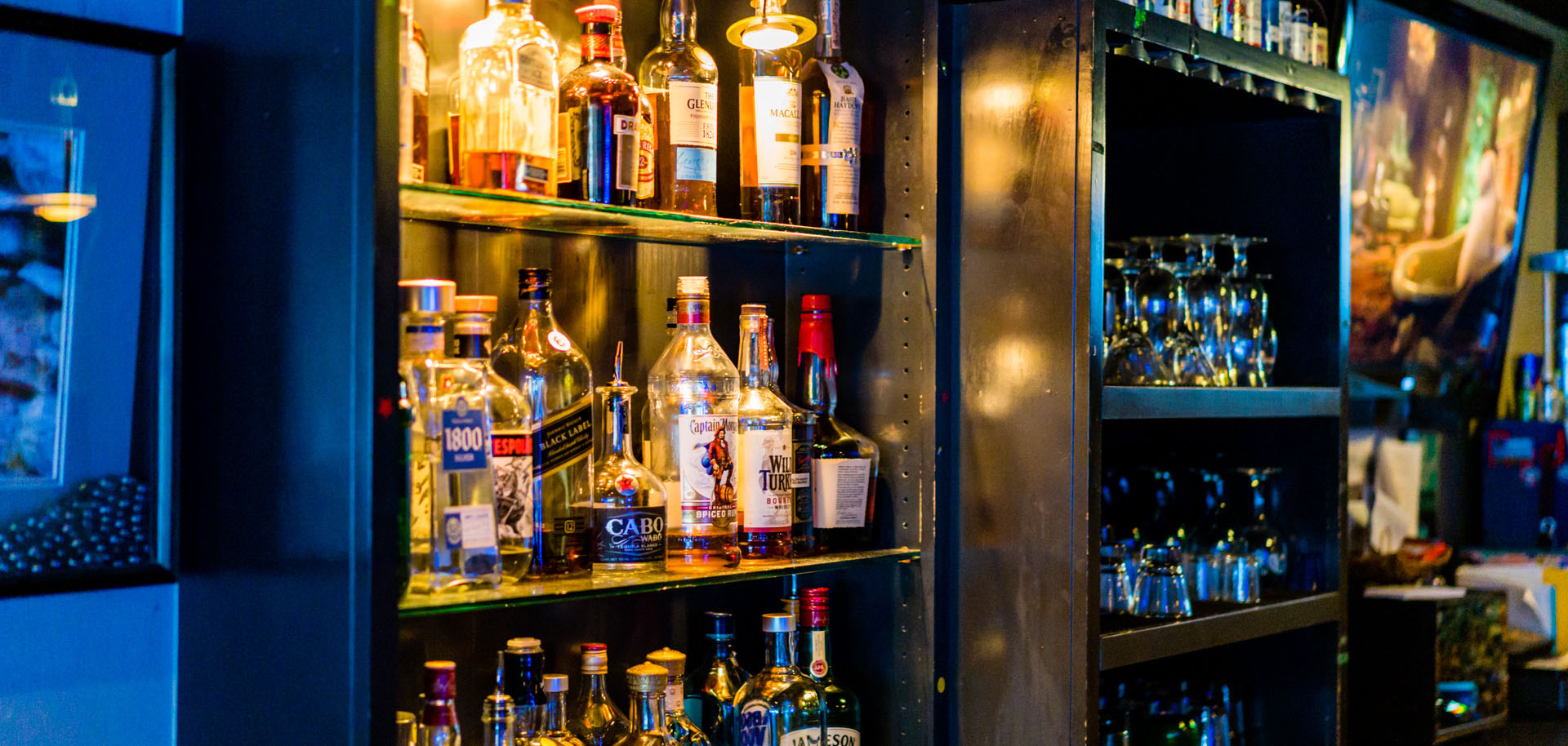 Alcohol behind the bar sits in an open bookcase at On The Rocks in Tulsa, Oklahoma.