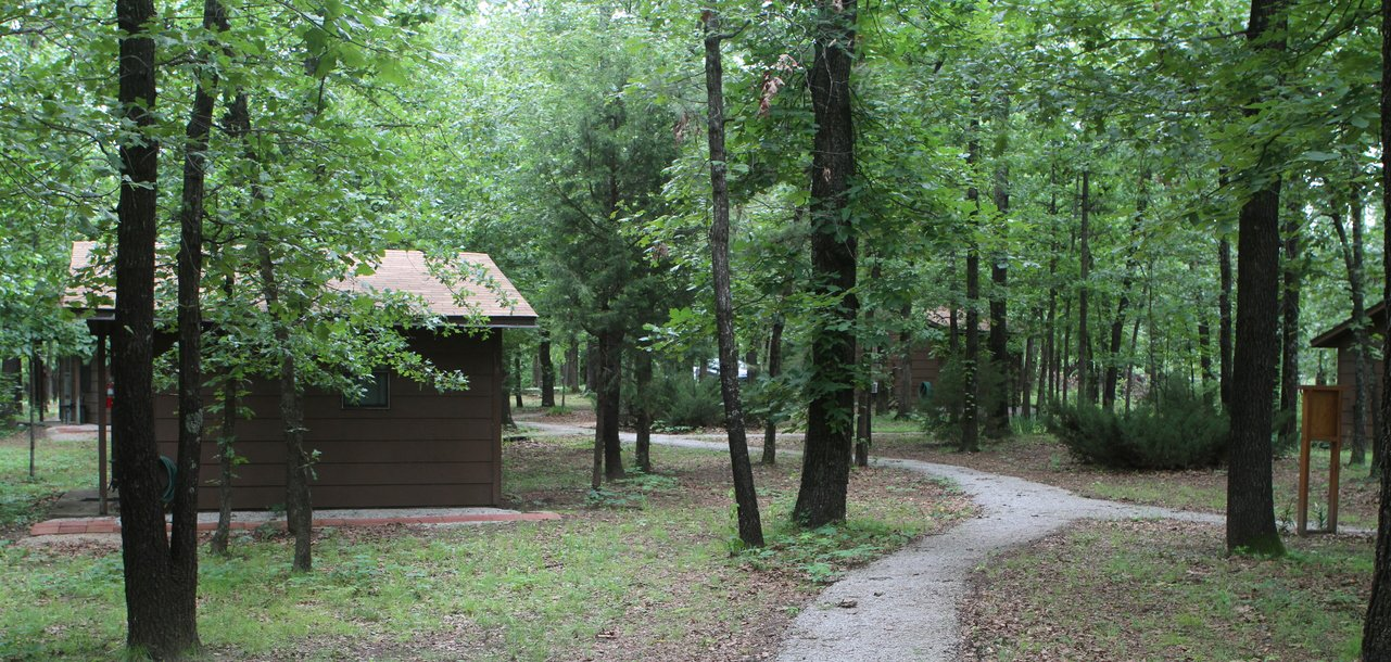 A path winds between trees and a cabin at Osage Forest of Peace near Tulsa, Oklahoma.