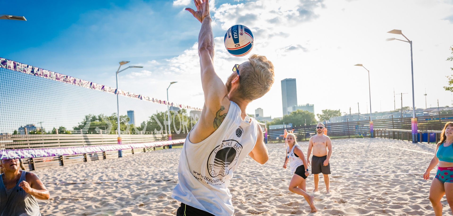 Sand volleyball players in action outside at Pearl Beach Brew Pub