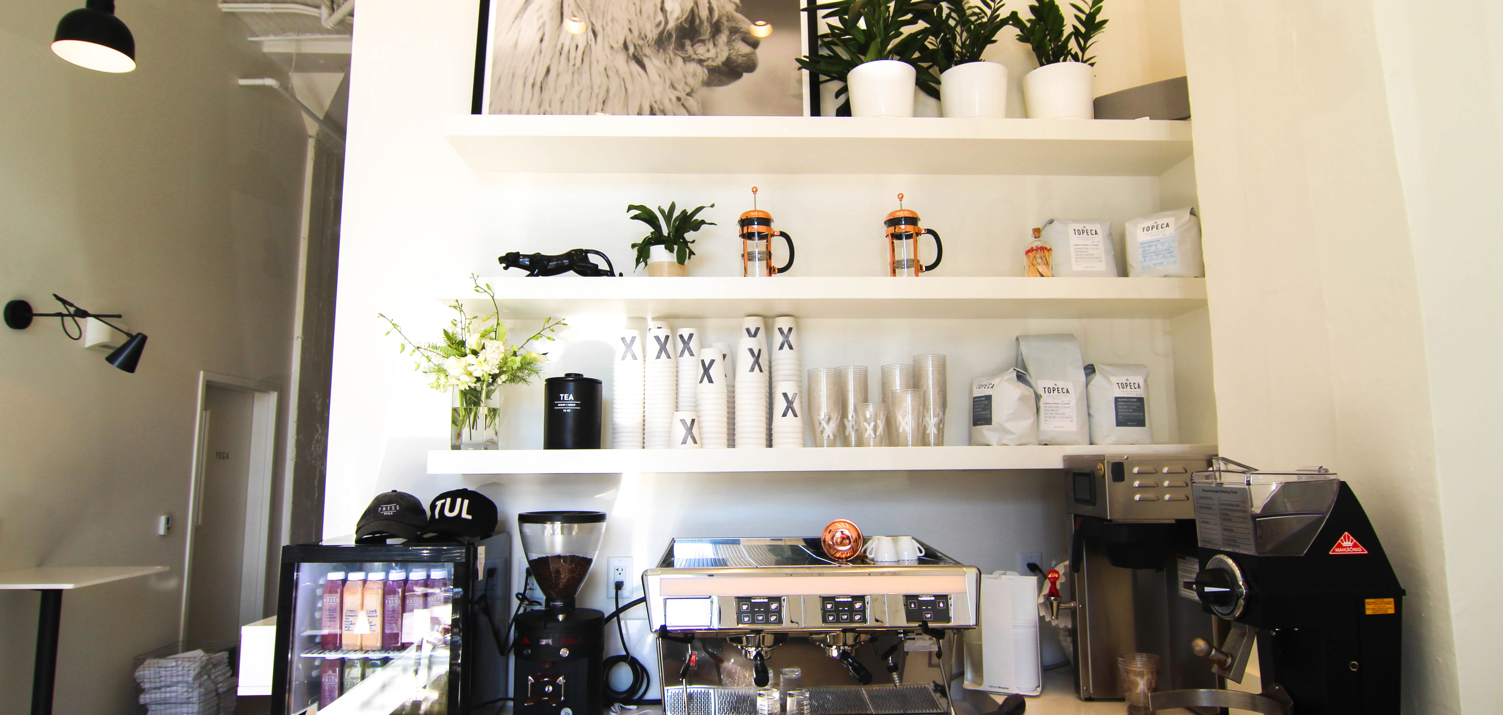 The interior of Press Cafe x Yoga is white and minimalist with stacks of their disposable coffee cups with a large black X.