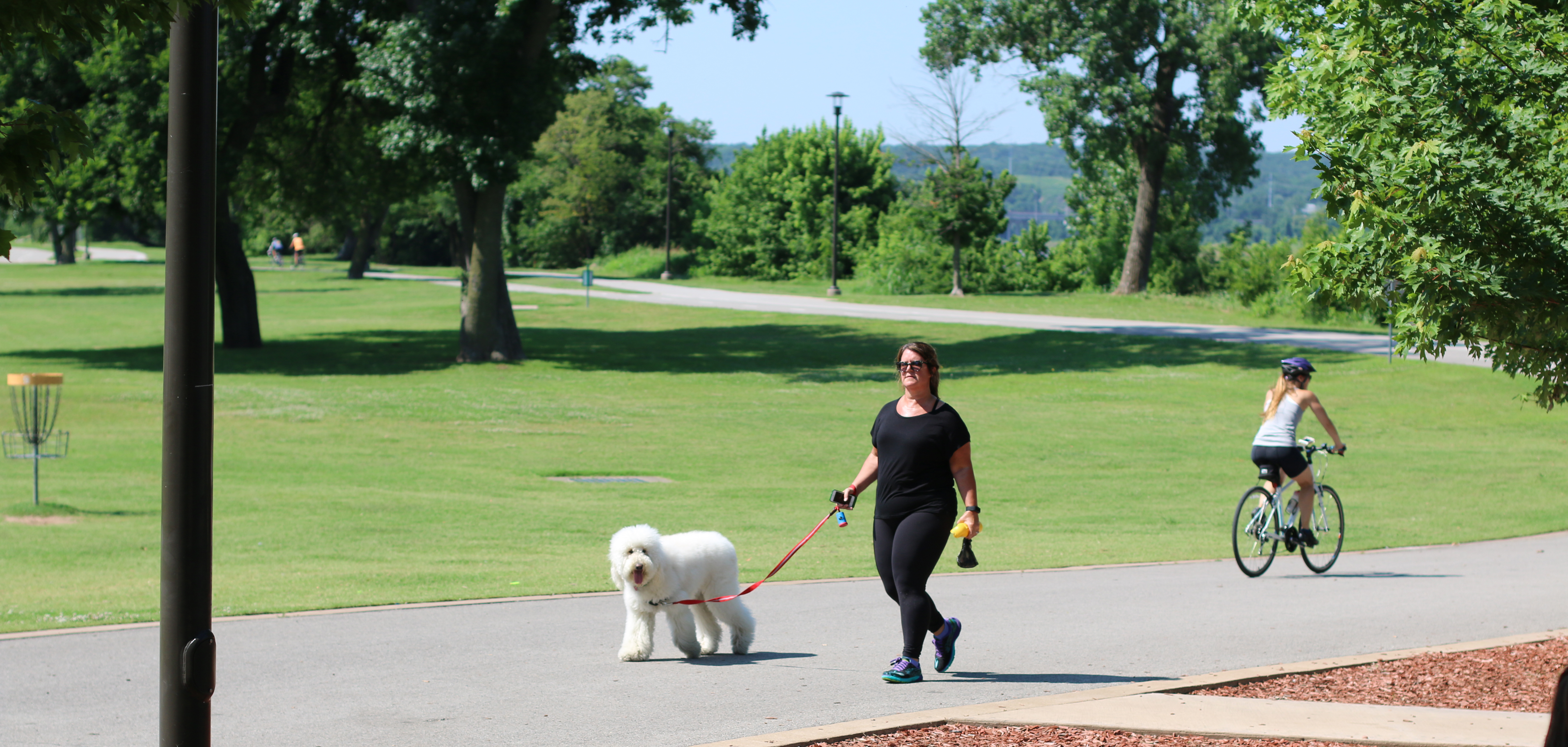 A woman walks a dog on the River Parks trail in Tulsa, Oklahoma.