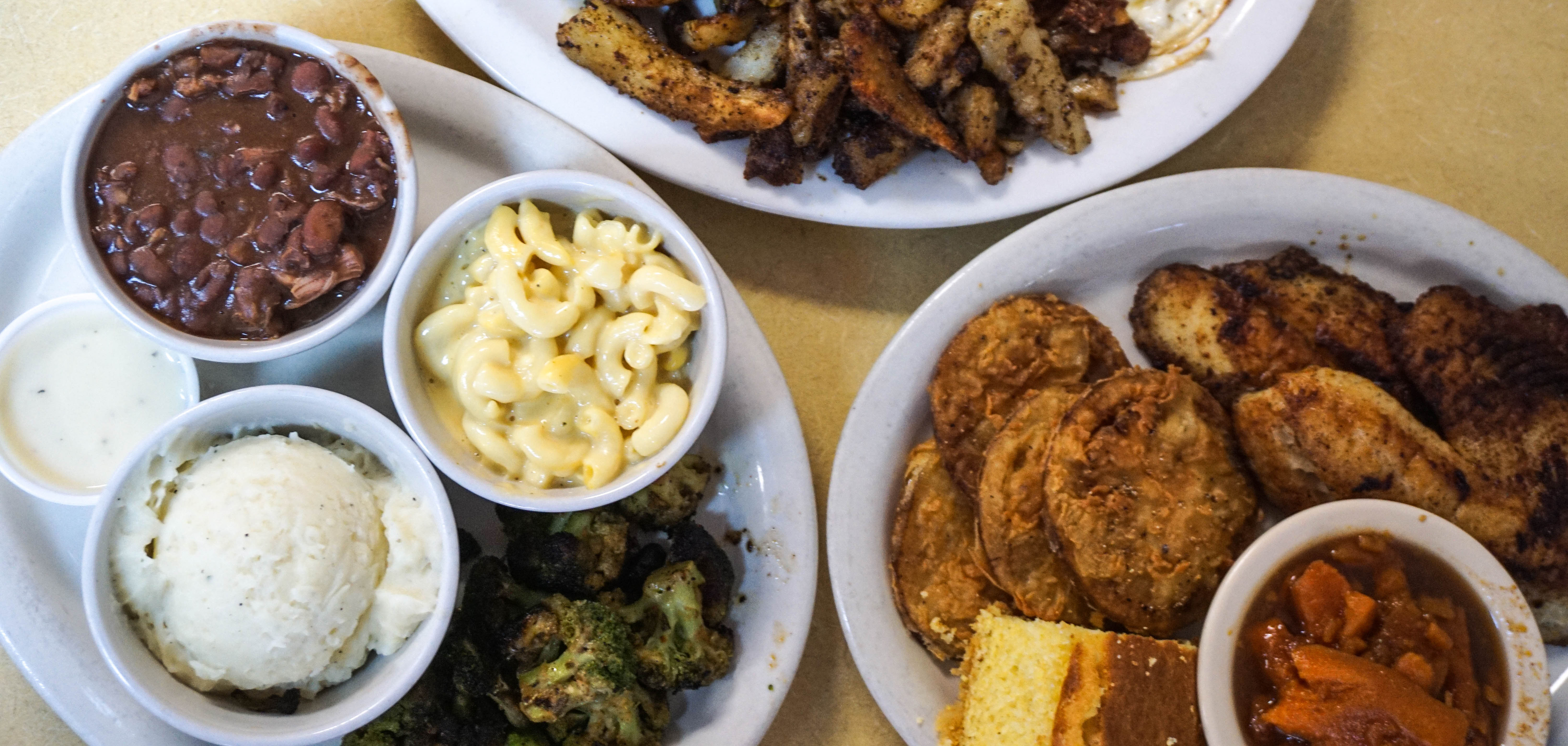 Two lunches at Sweet Lisas with mac and cheese, beans, mashed potatoes, fried green tomatoes, candied yams, chicken, and cornbread.