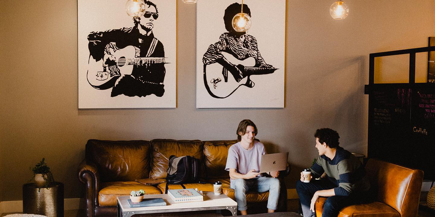 Two young adults sit on a couch talking at The Collab coffee shop.