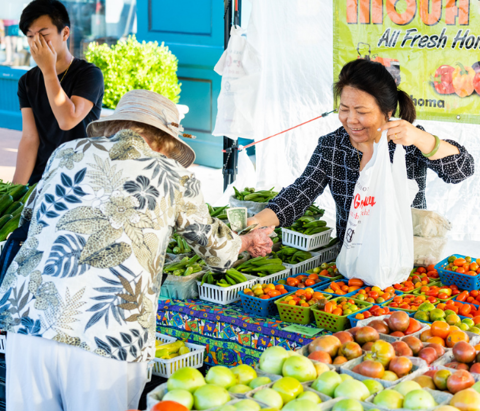 A customer purchases produce at the Tulsa Farmers' Market at Kendall Whittier Square in Tulsa, Oklahoma.