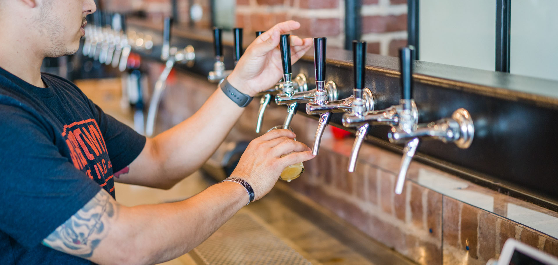 A bartender pours a beer from the tap at Welltown Brewing in the Tulsa Arts District.