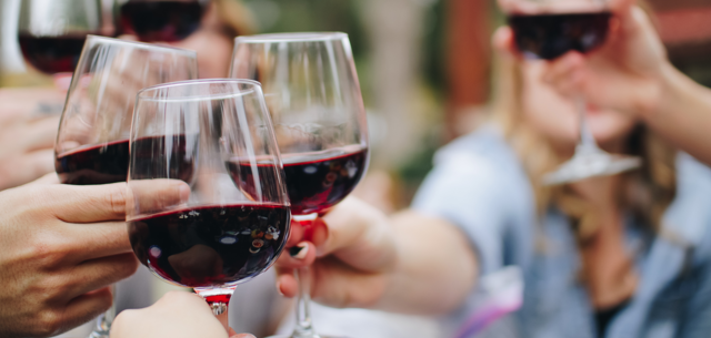People enjoy a glass of wine at a happy hour.