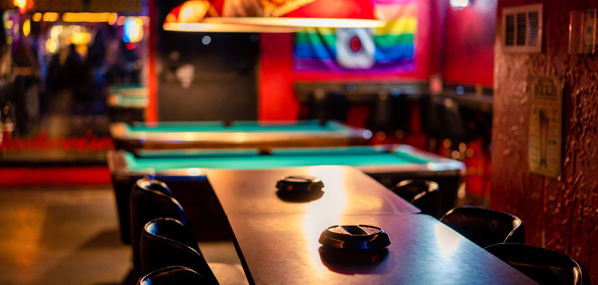 A table, two pool tables, and pride flag at Yellow Brick Road Pub in Tulsa, Oklahoma.