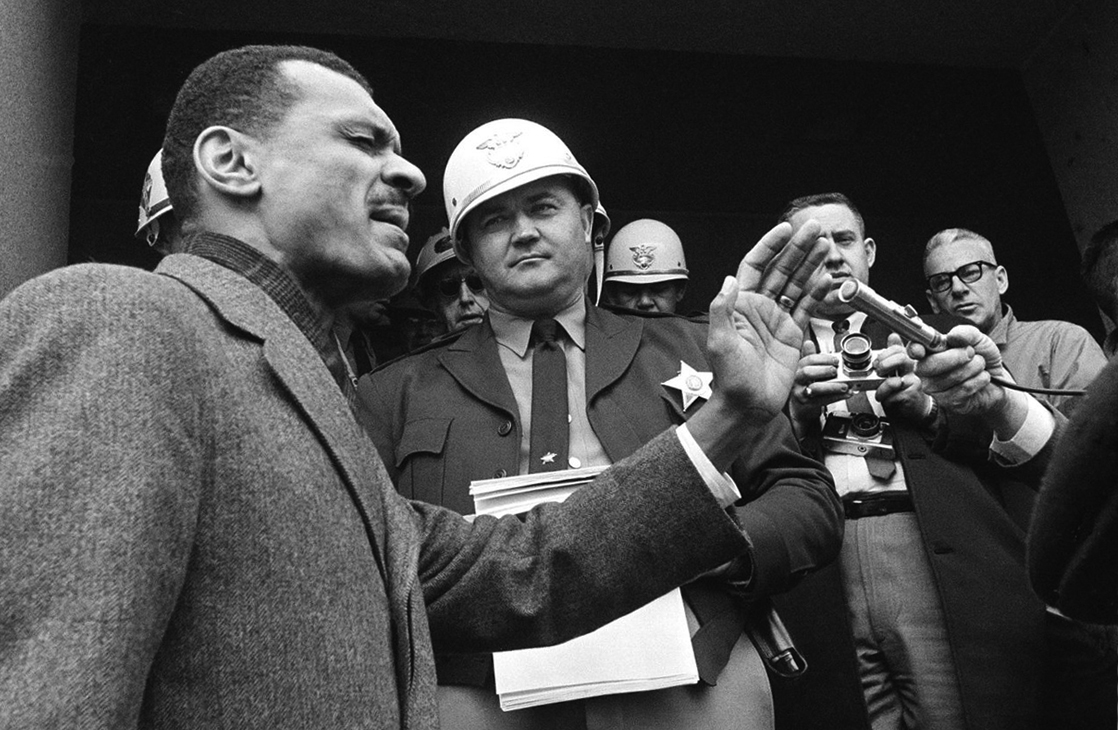 C. T. Vivian praying on the Dallas County courthouse steps before helmeted Sheriff Jim Clark stopped him at the door with a court order, Selma, Alabama, February 5, 1965. (Horace Court, AP)