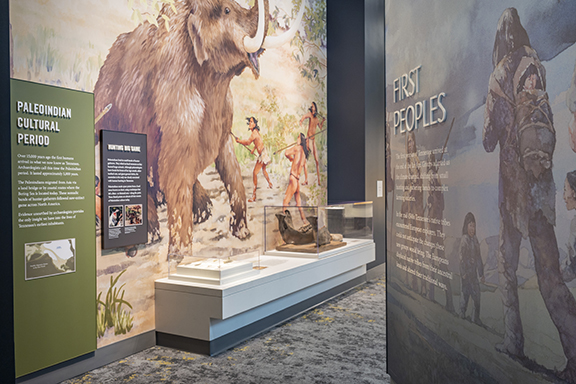 Installation View of First People's gallery at the Tennessee State Museum, with mural featuiring a mastodon, and a mastodon jawbone.
