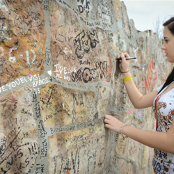 A must-do before leaving Graceland! This fan signs the famous wall.