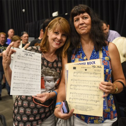 Fans show off the autographs they got after the Songwriters Showcase.