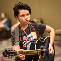 Finley strums his guitar in the music workshop.