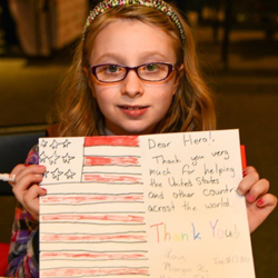 This Girl Scout shows off her thank-you letter to the troops.