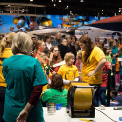 a crowd of people and women and children wearing yellow shirts in a plane hangar