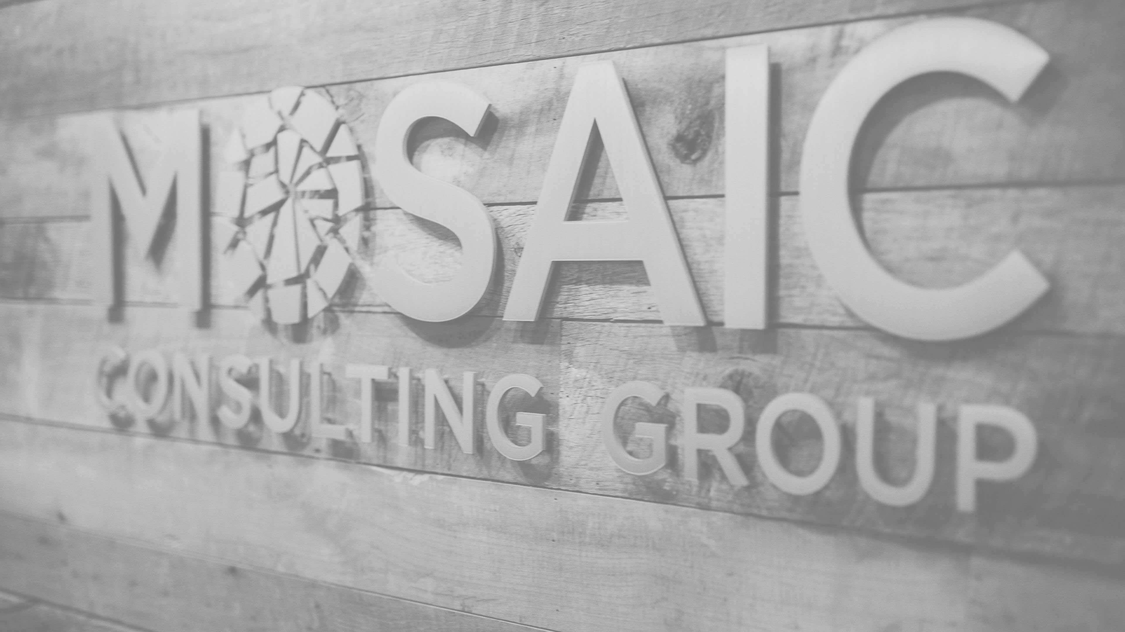 black and white photo of wooden boards and mosaic consulting group words