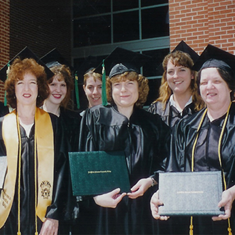 Graduates pose in caps and gowns