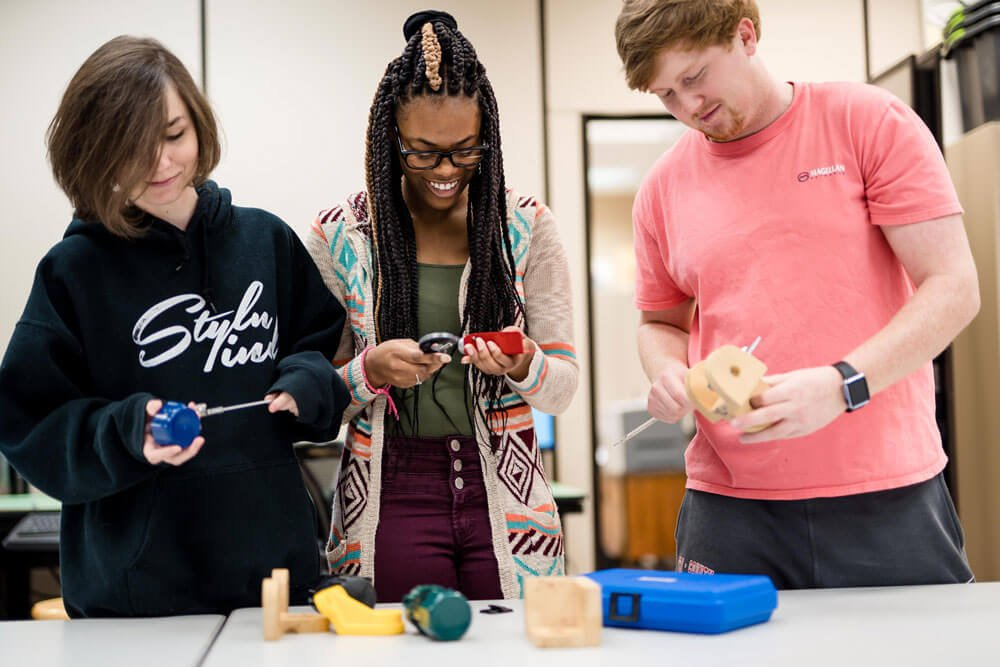 three adolescents working with tools in a classroom