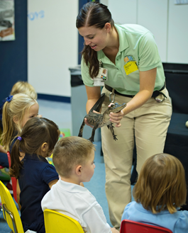 zookeeper introducing students to a lizard