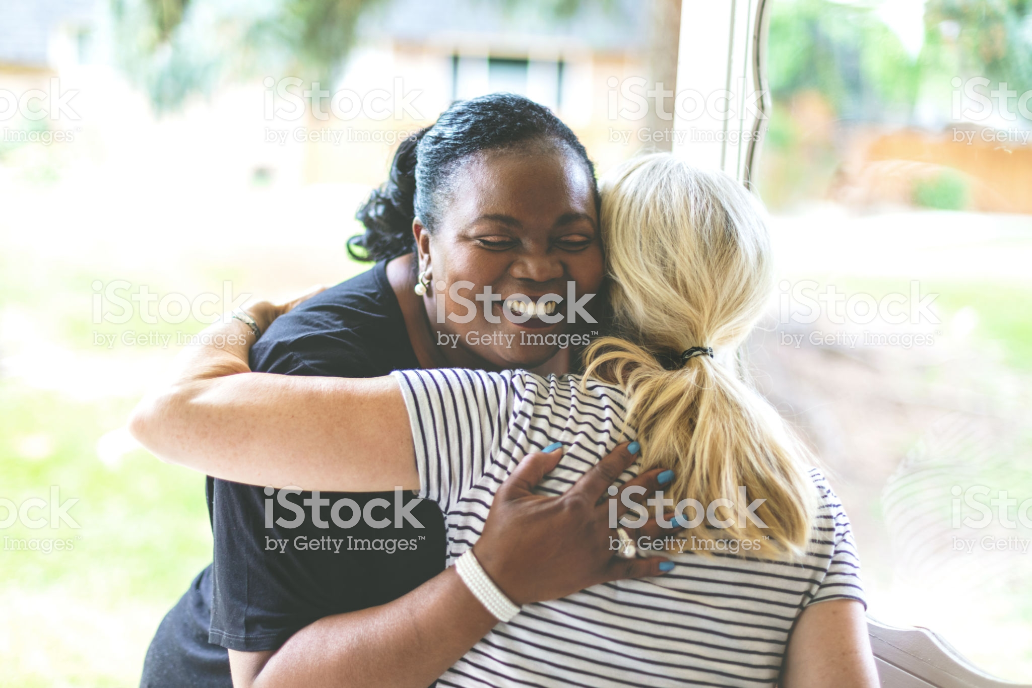 black woman and white woman hugging