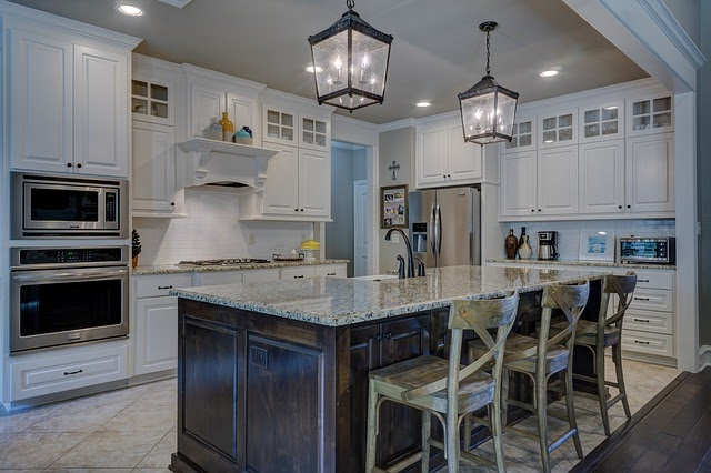 white painted kitchen with marble countertops and tile floors