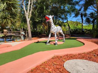 Zebra statue at a mini golf hole.