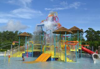 Water park with large overhead dump bucket splashing water.