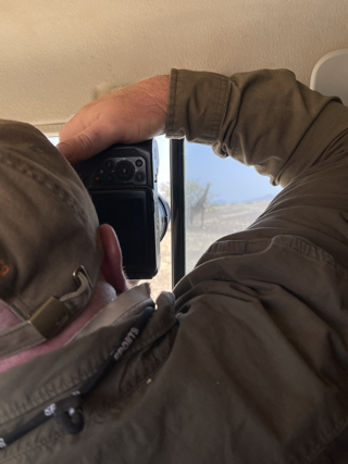 Wildlife team member Dave photographing a giraffe from inside of a truck.